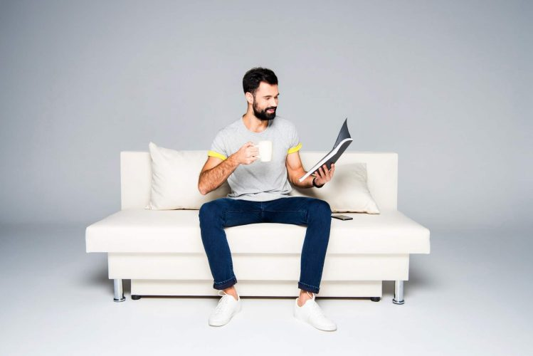 Bearded man sitting on couch and reading magazine while drinking coffee