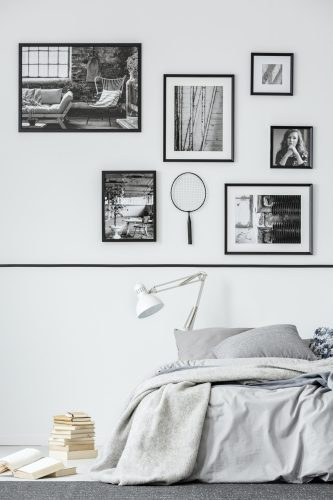 Books next to bed with white lamp in grey bedroom interior with